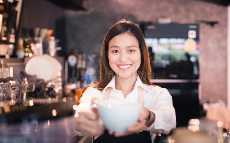 微笑与一杯咖啡的亚洲妇女barista在她的手上 库存图片