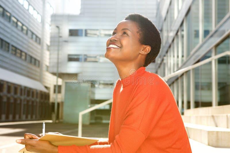 微笑与书和笔的愉快的年轻女人 免版税库存照片