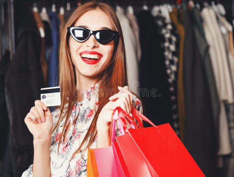 微笑与信用卡和购物袋的俏丽的妇女 免版税库存图片