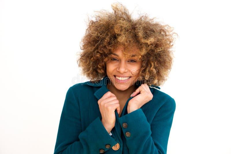 微笑与冬天外套的美丽的非裔美国人的女孩反对白色背景 免版税图库摄影