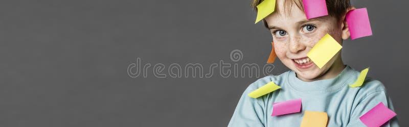 微笑与到处稠粘的笔记的逗人喜爱的繁忙的男孩,横幅 免版税库存照片