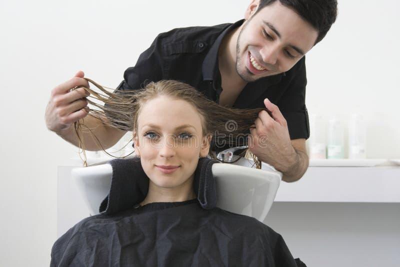 微笑与发式专家的妇女审查她的头发对沙龙 免版税图库摄影