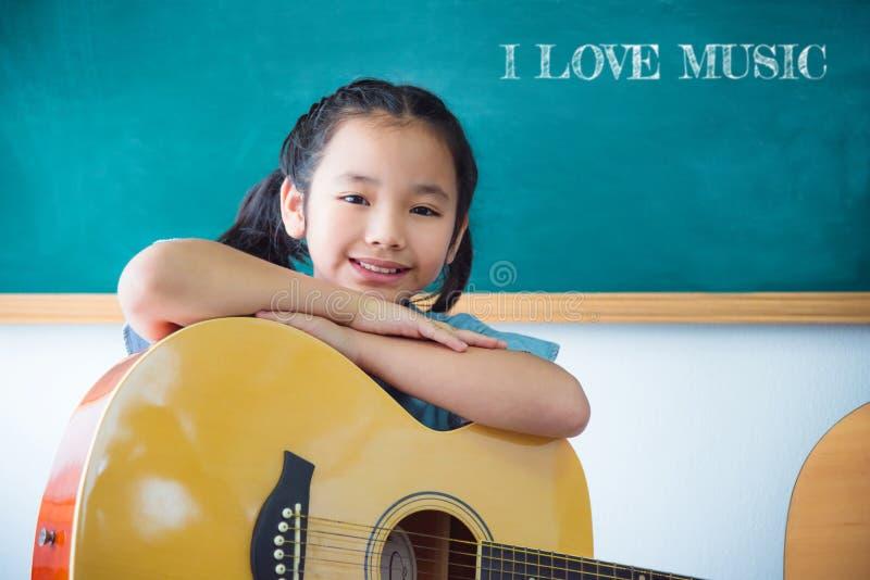 微笑与吉他的女孩在学校教室 库存图片