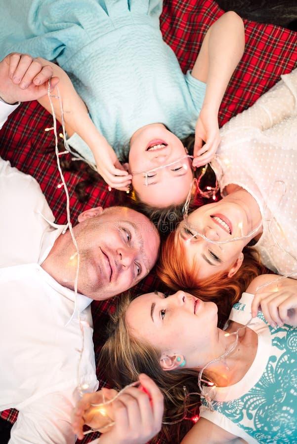 微笑与圣诞灯诗歌选的愉快的家庭在圣诞树附近 顶视图被修饰的射击  免版税图库摄影