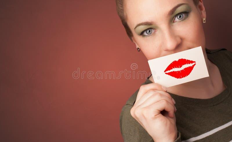 微笑与在他的嘴前面的一张卡片的人 免版税库存照片