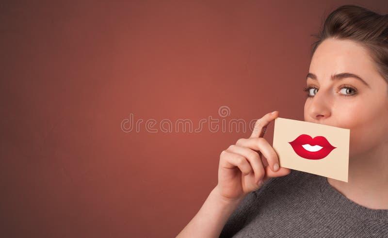 微笑与在他的嘴前面的一张卡片的人 库存照片