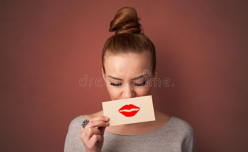 微笑与在他的嘴前面的一张卡片的人 免版税图库摄影