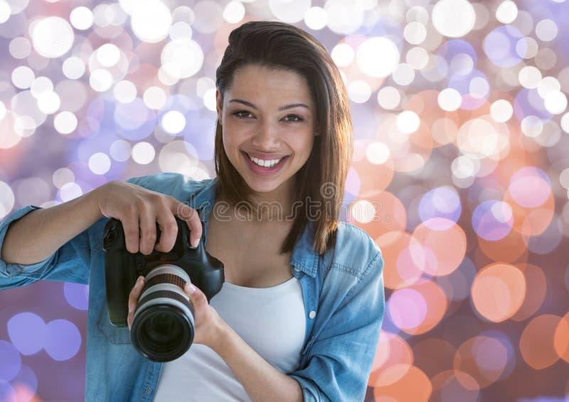 微笑与在手上的照相机的年轻摄影师 布朗白色和蓝色bokeh背景 免版税库存图片
