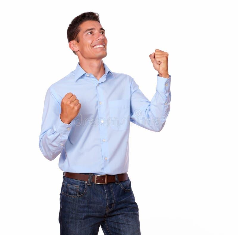 微笑与在胜利的胳膊的激动的年轻人。 免版税库存照片