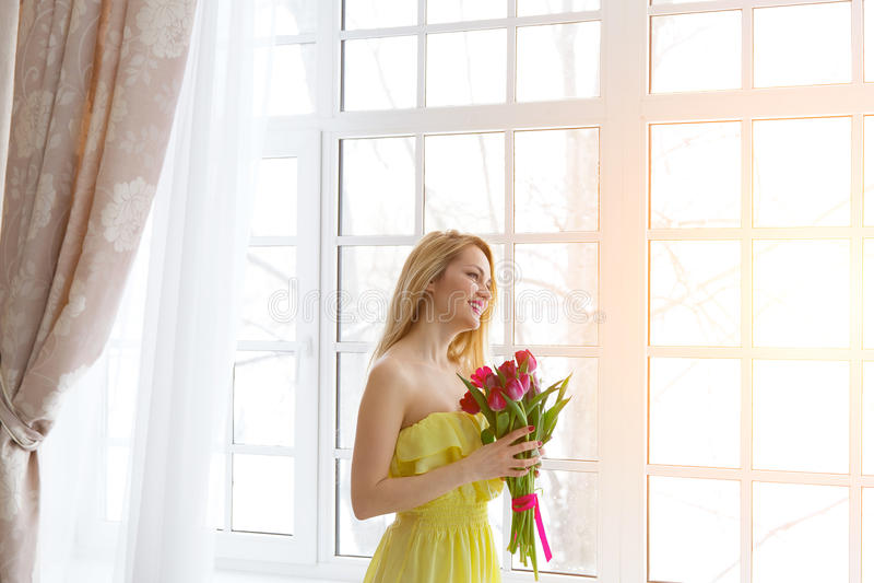 微笑与在黄色礼服的郁金香束,阳光的年轻愉快的妇女 免版税库存图片