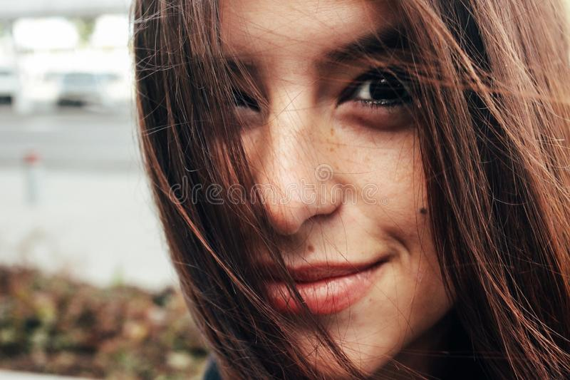 微笑与在backgro的雀斑的美丽的时髦的深色的女孩 库存照片