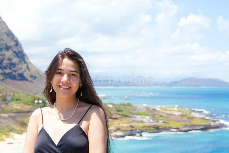 微笑与夏威夷海洋的愉快的青少年的女孩在背景中 图库摄影