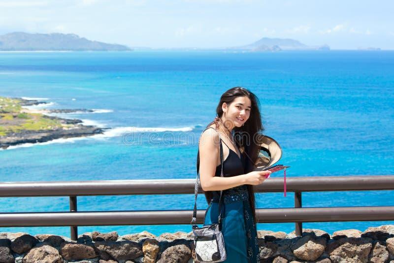 微笑与夏威夷海洋的愉快的青少年的女孩在背景中 免版税库存图片