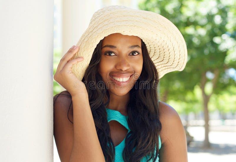 微笑与太阳帽子的可爱的非裔美国人的妇女 免版税库存图片