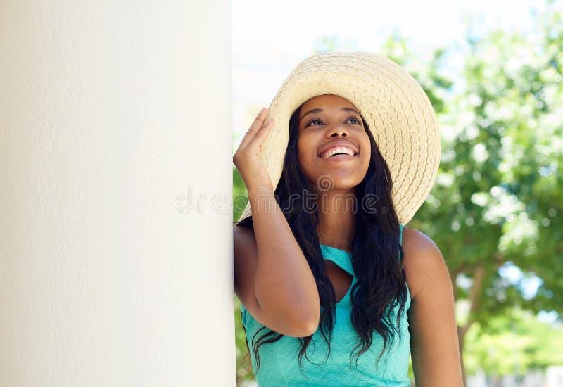 微笑与太阳帽子的逗人喜爱的非裔美国人的妇女 免版税库存照片