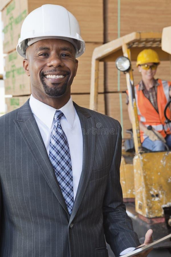 微笑与女工的非裔美国人的男性工程师画象在背景中 免版税库存照片