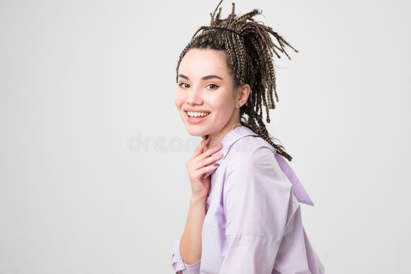 微笑与完善的微笑和白色牙的妇女 在猪尾做的她的头发 库存图片