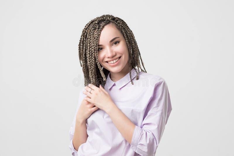 微笑与完善的微笑和白色牙的妇女 她的做的头发 免版税库存图片