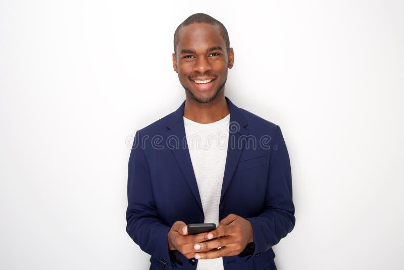 微笑与手机的凉快的年轻黑人反对白色背景 免版税库存照片