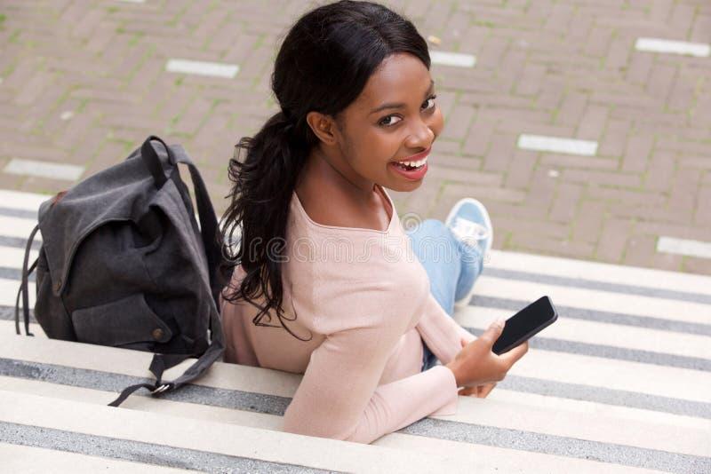 微笑与手机的后边年轻黑人妇女 免版税库存照片