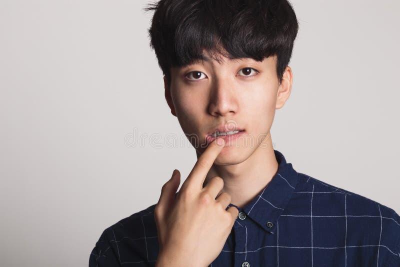 微笑与明亮的微笑的一个亚裔年轻人的演播室画象 免版税库存照片