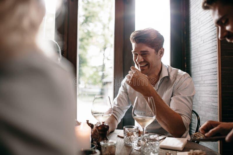 微笑与朋友的年轻人在餐馆 免版税库存图片