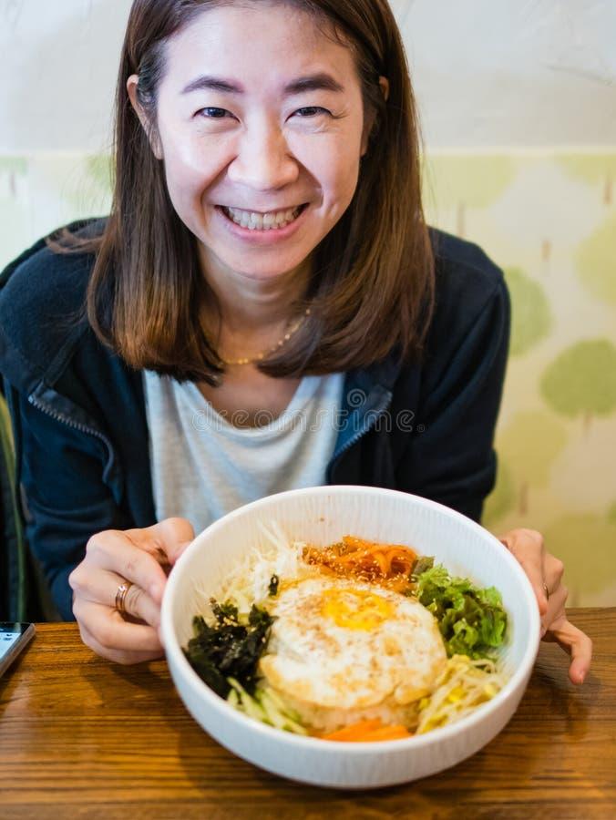 微笑与朝鲜拌饭的雍夫人 免版税库存照片