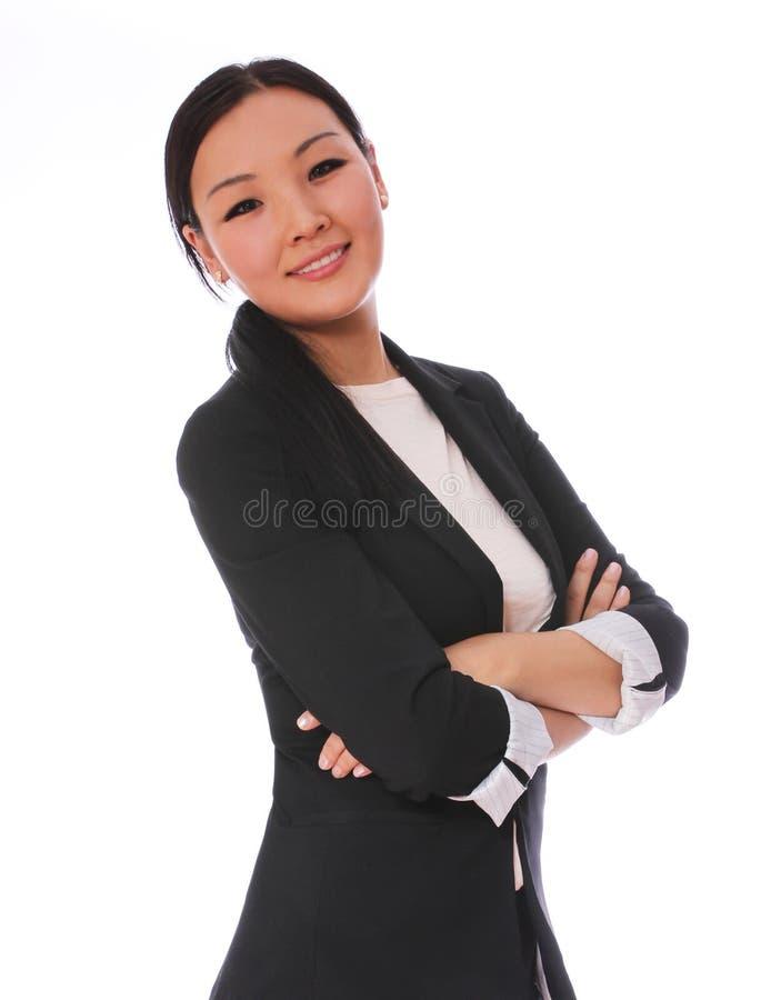 微笑与横渡的胳膊的女商人隔绝在白色背景。黑西装的美丽的亚裔妇女 图库摄影