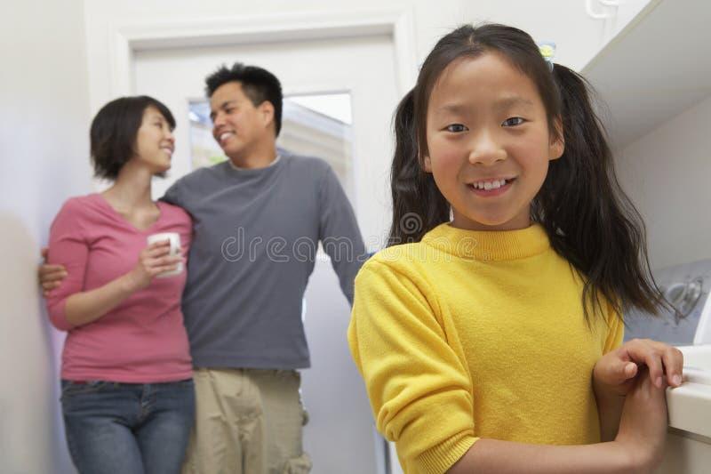 微笑与父母的少年在背景中 免版税库存图片