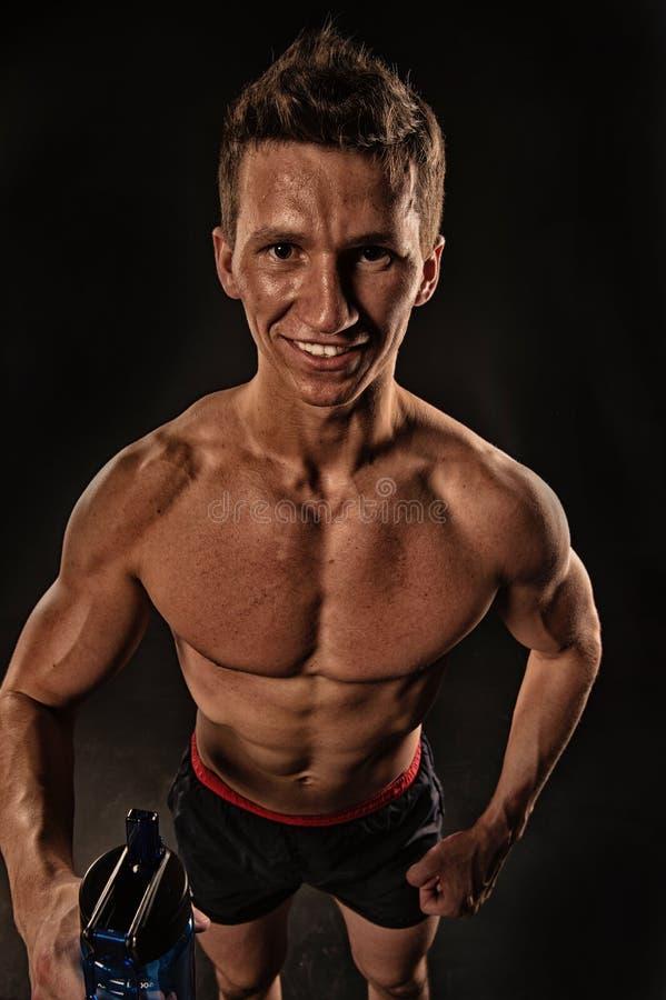 微笑与瓶的渴运动员水 与体育瓶的运动员微笑 有适合的身体和躯干的愉快的人 库存图片