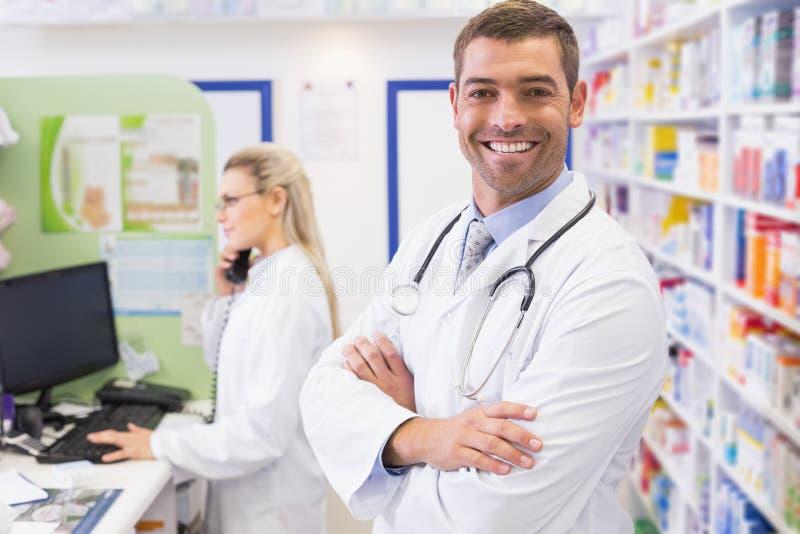 微笑与电话的药剂师的药剂师 免版税库存图片