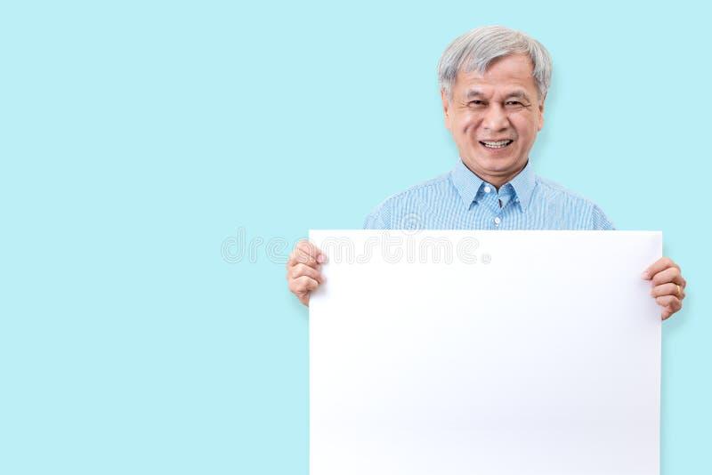 微笑与白色牙的愉快的祖父,享用片刻和拿着一个空白的委员会 显示您的亚裔更老的人白空白的委员会 图库摄影