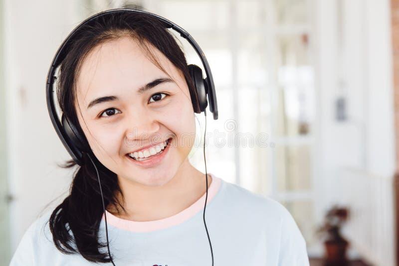 微笑与耳机的亚裔逗人喜爱的少女青少年 免版税库存照片图片
