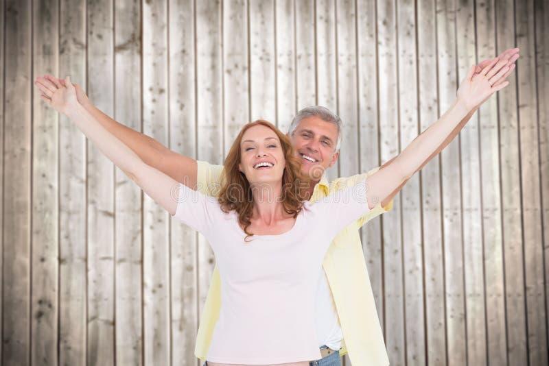 微笑与胳膊的偶然夫妇的综合图象被举 图库摄影