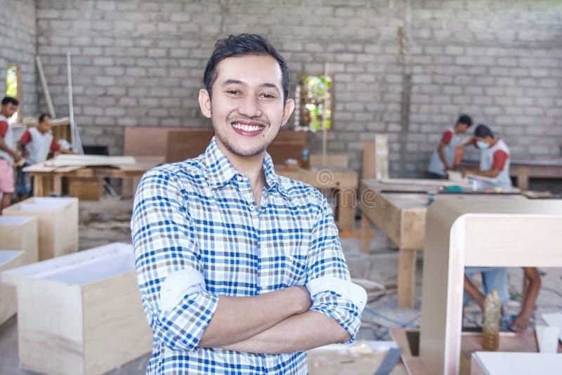 微笑与胳膊的年轻木匠在木匠车间横渡了 免版税库存照片