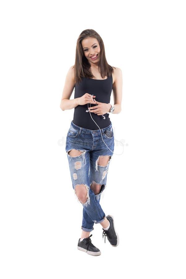 微笑与舌头的迷人的俏丽的年轻女人,当拿着手机耳机时 免版税图库摄影