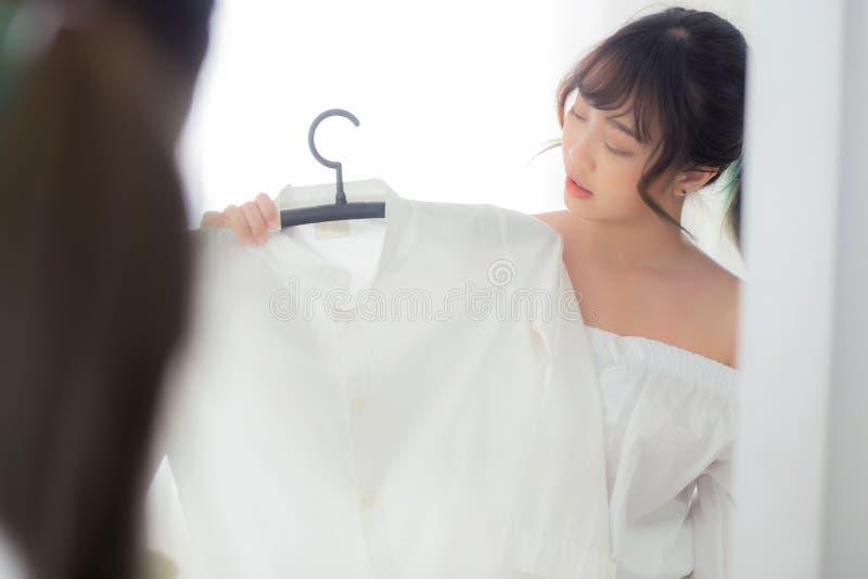 微笑与衣裳的美丽的年轻亚裔妇女尝试在符合现代和看的反射镜子的礼服在屋子里 免版税图库摄影