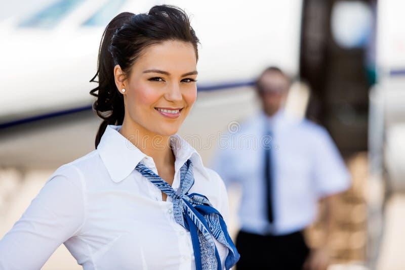 微笑与试验和私人喷气式飞机的空中小姐  免版税图库摄影
