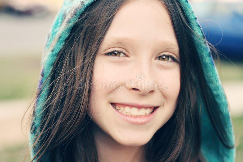 微笑与长的头发和帽子的女孩 免版税库存照片