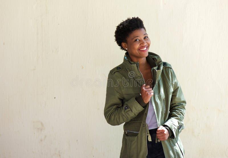 微笑与高尔夫球外套的凉快的非裔美国人的妇女 图库摄影