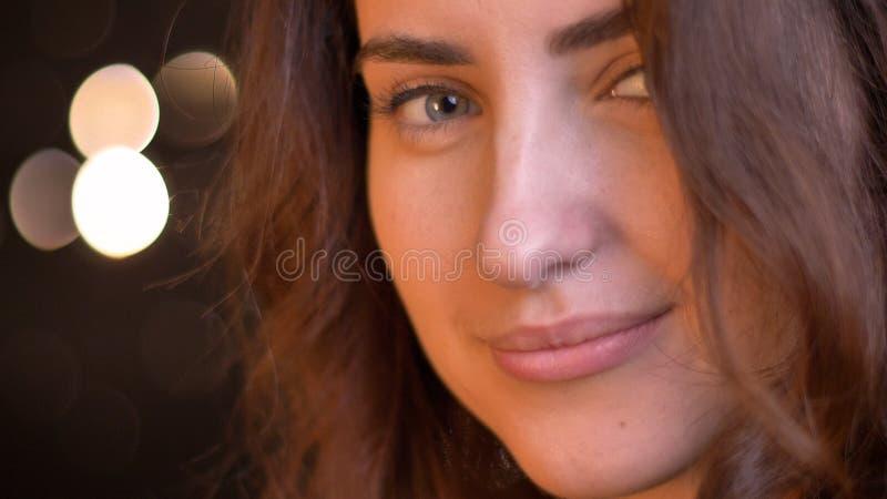 微笑与魅力的年轻诱人的白种人女性特写镜头射击,当看直接与bokeh光时的照相机 免版税库存照片