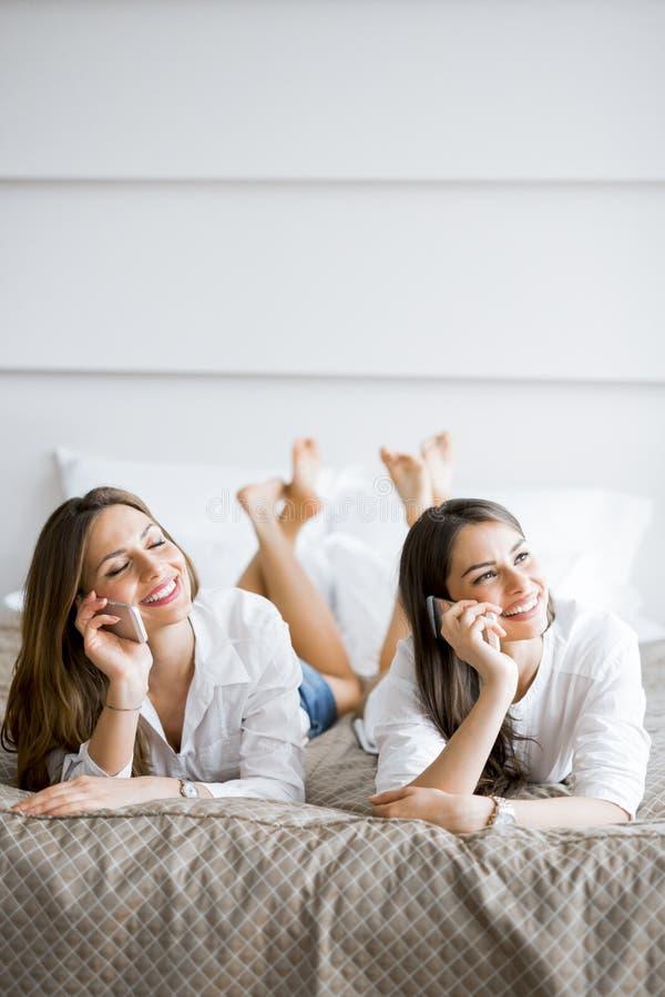 微笑两个美丽的女孩谈话和,当躺在床上时 图库摄影