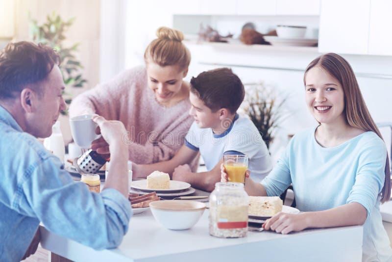 微笑为照相机的愉快的十几岁的女孩在家庭早餐期间 免版税图库摄影