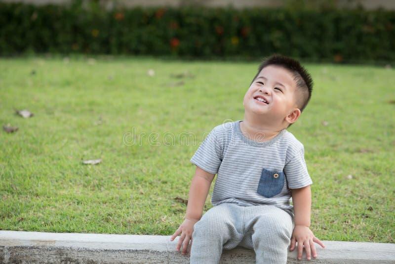 微笑亚裔男婴画象坐在小径边缘的在公园 库存照片