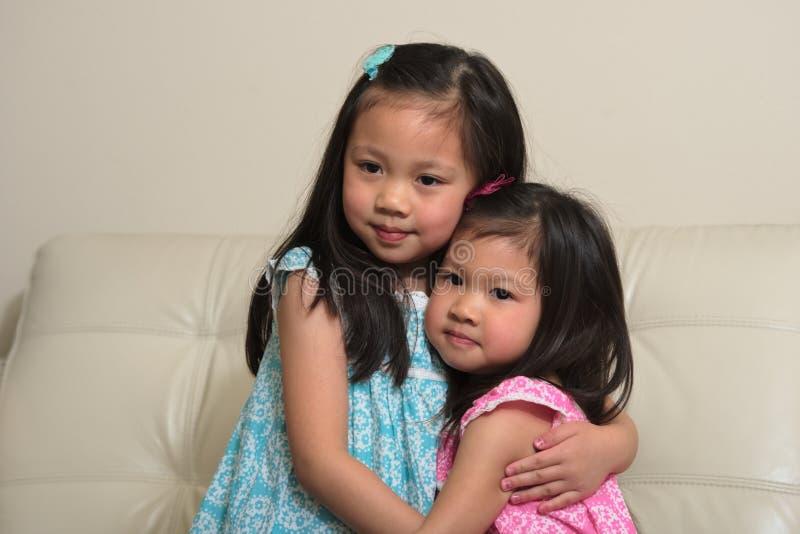 微笑亚裔的姐妹拥抱和 库存图片