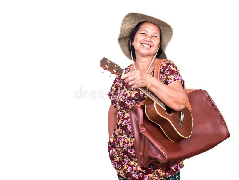 微笑亚裔senoir的妇女,当运载尤克里里琴和大褐色时 库存图片