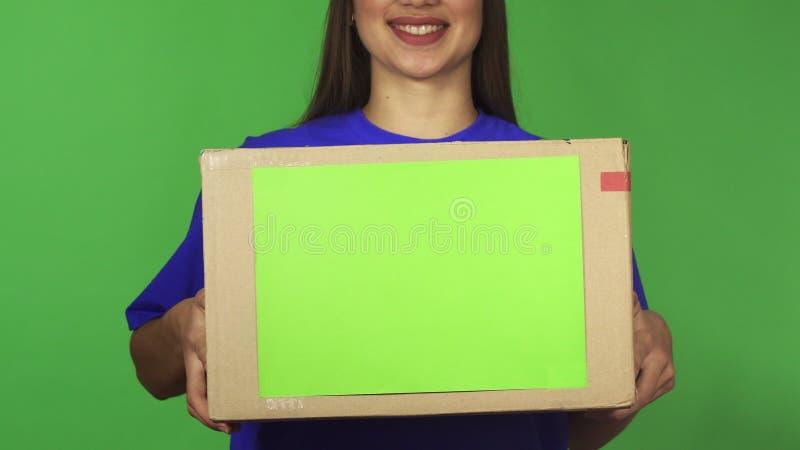 微笑交付的妇女的播种的射击拿着有copyspace的carboard箱子 图库摄影