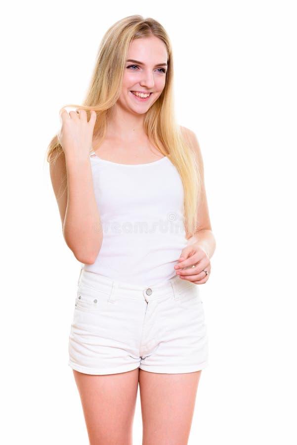 微笑体贴的年轻愉快的十几岁的女孩,当使用与h时 图库摄影