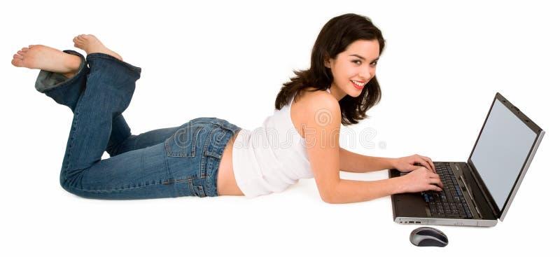 微笑使用妇女年轻人的楼层膝上型计算机 图库摄影