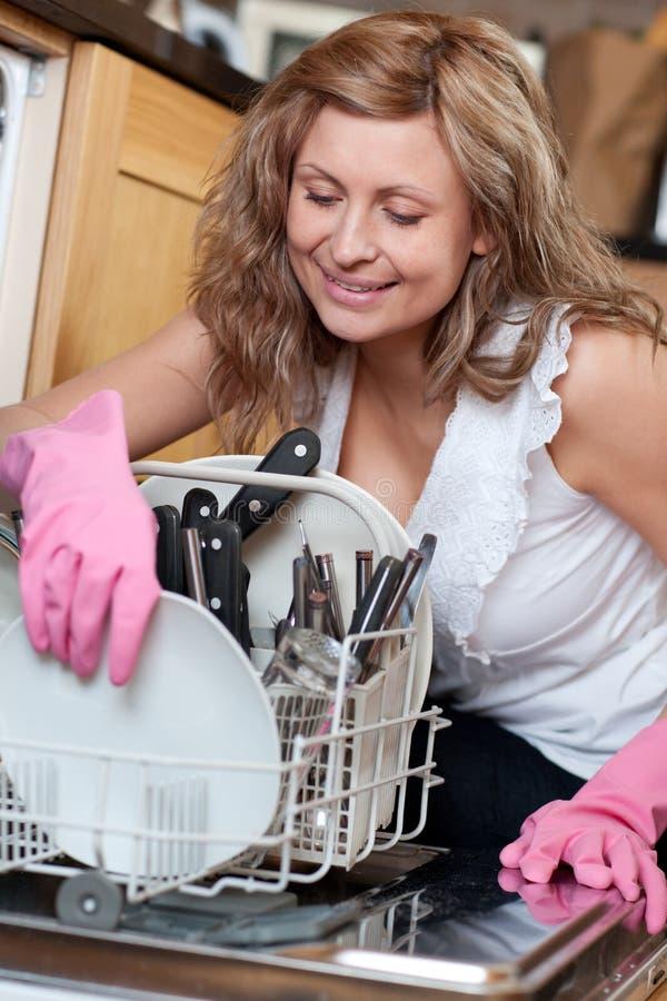 微笑使用妇女年轻人的洗碗机 库存照片